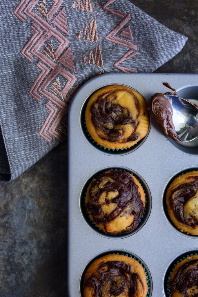 muffins with swirls of nutella on top in a six cavity muffin tin