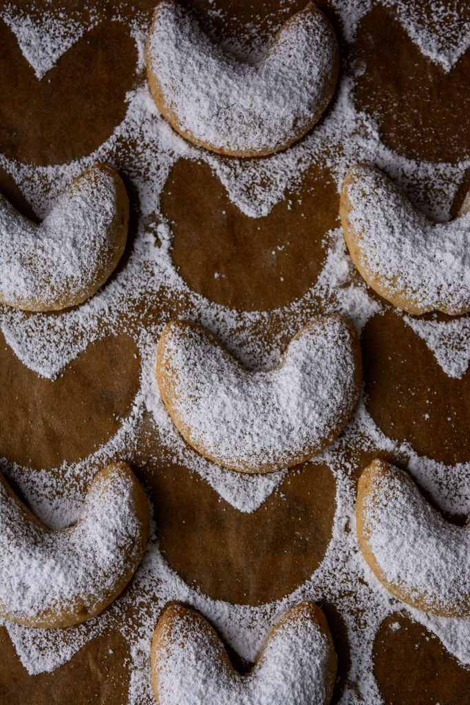 crescent shaped cookies dusted with powdered sugar on brown parchment paper