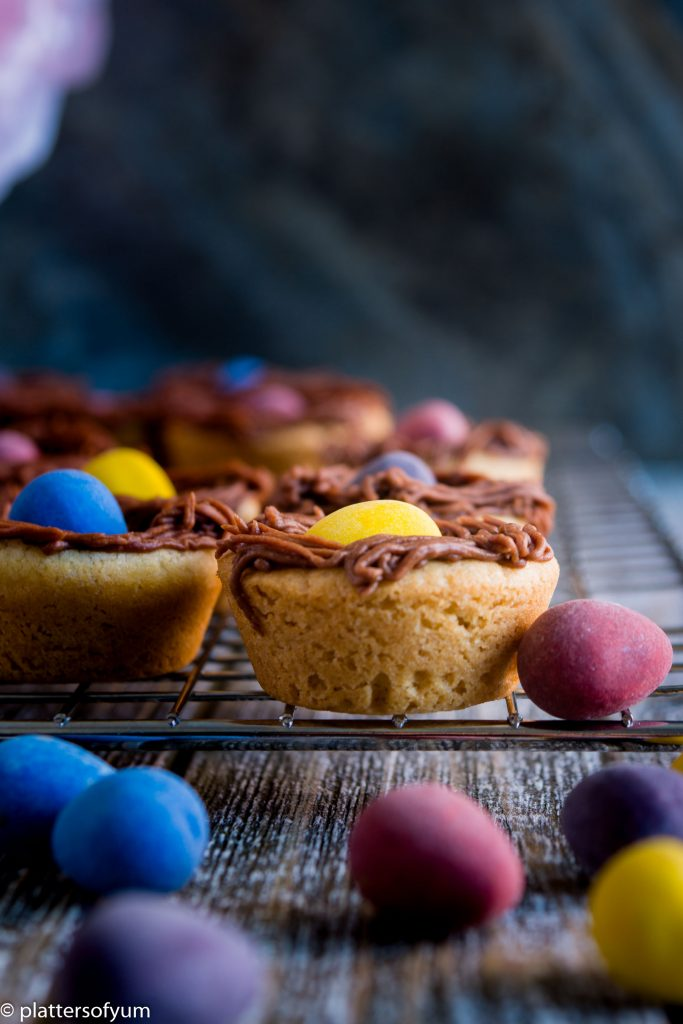sugar cookie cups with different colors of mini egg chocolates on a cooling rack and chocolate eggs lying near them