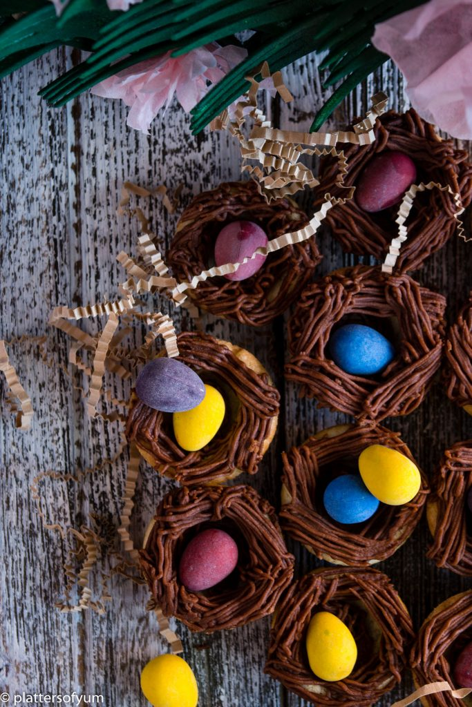 Sugar cookies cups with chocolate buttercream nests and colorful mini chocolate eggs on top on a wooden surface.